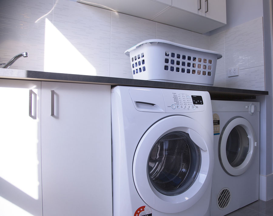 An Australian home laundry with washing machine, clothes dryer and washing basket.